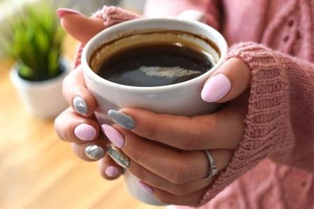 温かいコーヒーを手に持つ女性